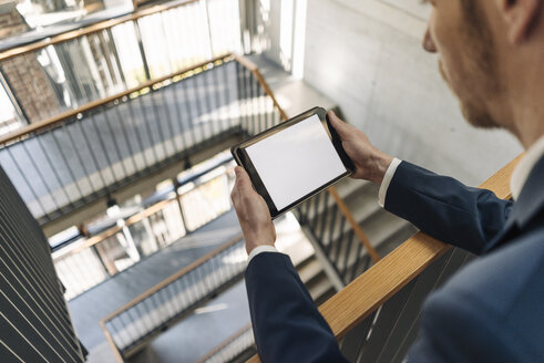 Businessman using tablet in staircase - KNSF01168