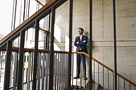 Smiling businessman standing in staircase - KNSF01171