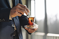 Businessman holding glass of Turkish tea - KNSF01177