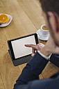 Businessman using tablet on table - KNSF01186