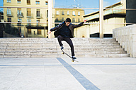 Young man riding skateboard in the city - KKAF00504