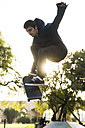 Young man with skateboard jumping in the air - KKAF00513