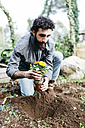 Man planting flowers in his garden - JRFF01260