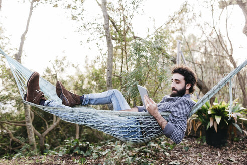 Man lying in hammock using tablet - JRFF01284