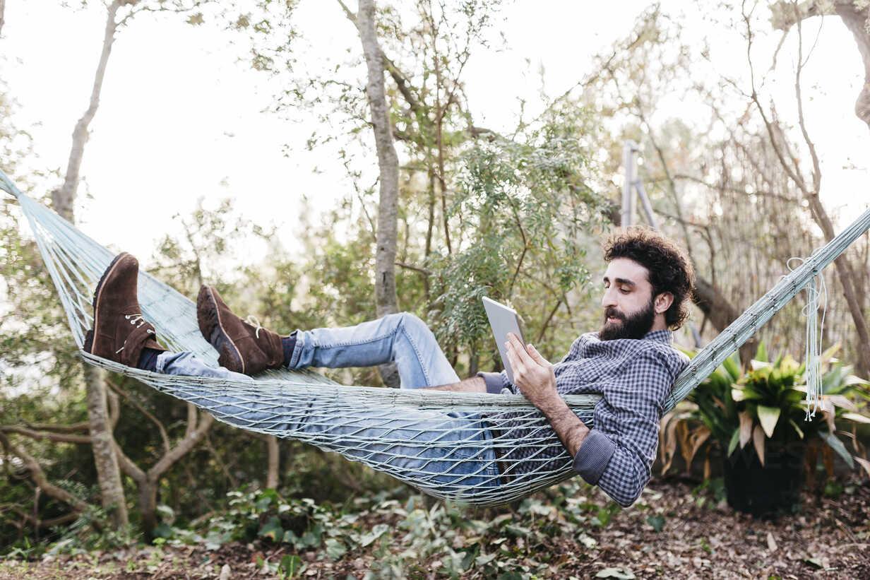 Man lying in hammock using tablet - JRFF01284 - Josep Rovirosa/Westend61