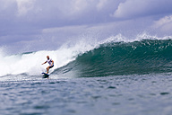Indonesia, Bali, man surfing on a wave - KNTF00751