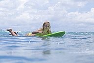 Indonesia, Bali, woman lying on surfboard in the ocean - KNTF00754