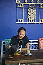 Indonesia, woman looking at dish in a cafe - KNTF00764