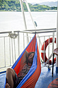Indonesia, Lombok island, man lying in hammock on ship deck - KNTF00767