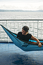 Indonesia, Lombok island, smiling woman in hammock on ship deck - KNTF00770