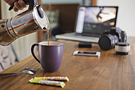 Photographer pouring coffee into cup at desk at home - KNTF00775