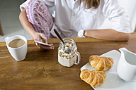 Woman at breakfast table using cell phone - KNTF00787