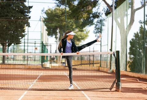 Teenage girl warming up on tennis court - VABF01262