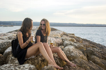 Indonesia, Bali, two women having a beer at the coast - KNTF00791