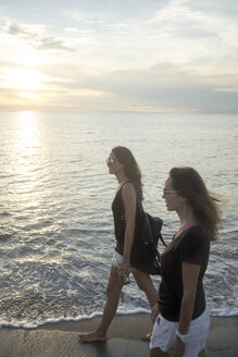 Indonesia, Bali, two women walking on the beach at sunset - KNTF00794