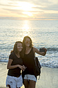 Indonesia, Bali, two women taking a selfie on the beach at sunset - KNTF00797