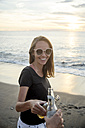 Indonesia, Bali, happy woman clinking beer bottle with friend on the beach at sunset - KNTF00800
