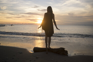 Indonesia, Bali, woman watching the sunset over the ocean - KNTF00803