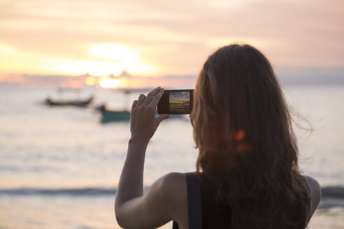 Indonesia, Bali, woman taking a picture of the sunset over the ocean - KNTF00806