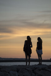 Indonesia, Bali, two women watching the sunset over the ocean - KNTF00809