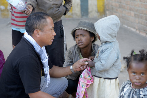 Madagascar, Fianarantsoa, Social worker talking to a homeless young mother and her child - FLKF00783