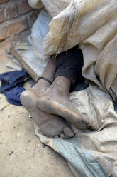 Madagascar, Fianarantsoa, Bare feet of a homeless person sleeping under rags - FLKF00789