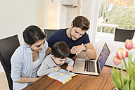 Family with laptop and guidebook planning vacation at home - SHKF00723