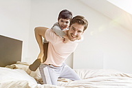 Happy father and son playing in bed - SHKF00732