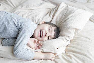 Happy boy lying in bed - SHKF00735