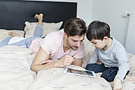 Father and son looking at tablet in bed - SHKF00738
