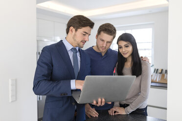 Consultant with laptop talking to couple at home - SHKF00750