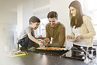 Family preparing pizza in kitchen together - SHKF00753