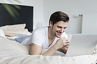 Smiling man lying on bed using laptop - SHKF00756