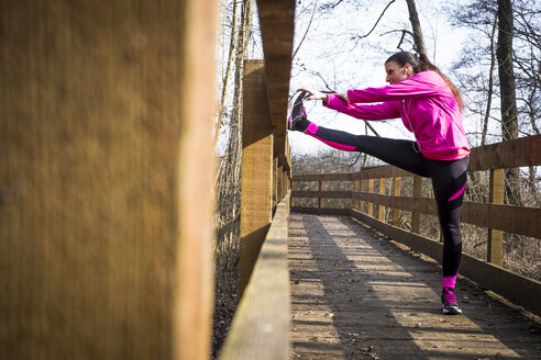 Woman stretching on wooden bridge in forest - SIPF01444