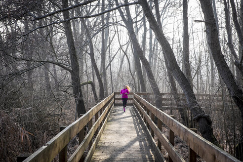 Woman running on wooden bridge through forest - SIPF01447
