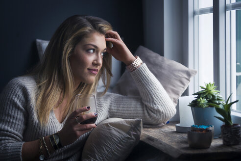 Young woman with glass of coffee sitting on couch at home looking through window - NAF00060
