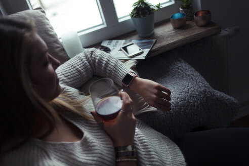 Young woman with glass of coffee relaxing on couch at home looking at smartwatch - NAF00063