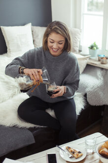 Smiling blond woman sitting on the couch pouring coffee into a glass - NAF00066