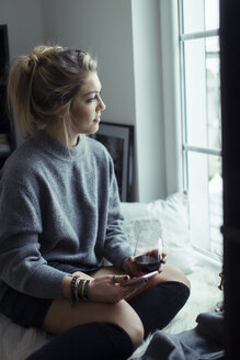 Young woman with cup of coffee and smartphone looking through window - NAF00075