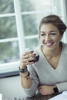 Portrait of smiling young woman with glass of coffee - NAF00081