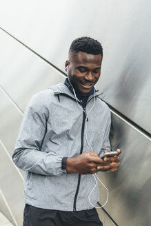 Athlete at building front with earbuds looking at cell phone - BOYF00675