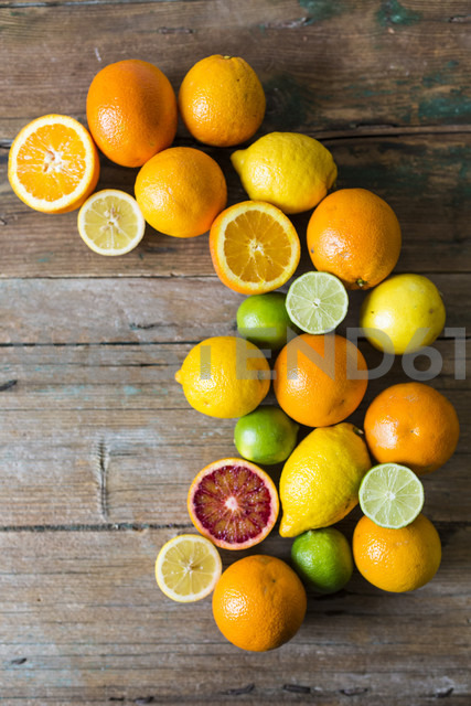 Sliced and whole lemons, oranges and limes on wood - GIOF02236