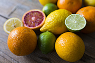 Sliced and whole limes, oranges and lemons on wood - GIOF02239