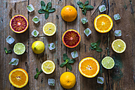 Sliced and whole lemons, oranges and limes, mint leaves and ice cubes on wood - GIOF02242