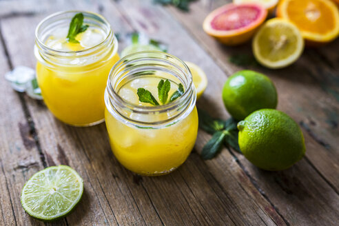 Two glasses of orange juice, limes, lemon and ice cubes - GIOF02248