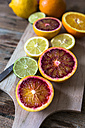 Sliced lemon, oranges and lime on wooden board - GIOF02251
