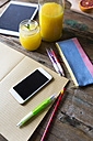 Glass of orange juice, notepad, pencils, pencil case, tablet and cell phone - GIOF02254