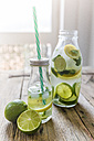 Glass bottles of infused water with lemon, lime, mint leaves and ice cubes - GIOF02266
