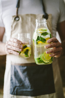 Man's handsholding glass bottle of infused water with lemon, lime, mint leaves and ice cubes - GIOF02272