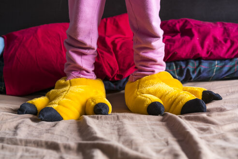 Girl standing on bed wearing yellow fun slippers - XCF00149